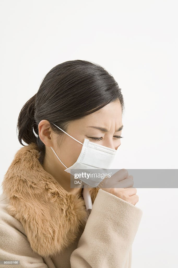 Woman wearing a mask coughing : Stock Photo