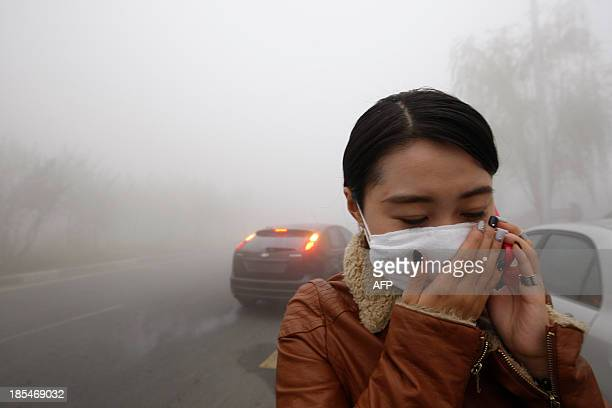 A woman wearing a mask covers her mouth with her hands as she walks in the smog in Harbin northeast China's Heilongjiang province on October 21 2013...
