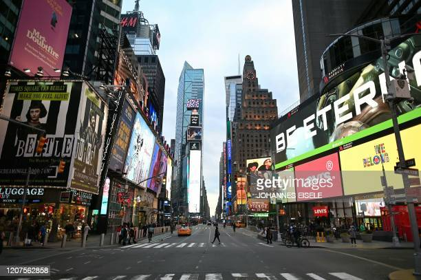 A woman wearing a mask crosses the street in Times Square in Manhattan on March 17 2020 in New York City The coronavirus outbreak has transformed the...