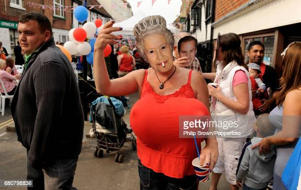 A woman wearing a mask depicting the Queen waves during a street party in Eton High Street near Windsor Castle on the day that Kate Middleton married...