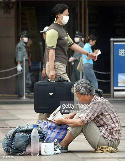 A woman wearing a mask for protection from the Severe Acute Respiratory Syndrome virus walks past a migrant worker sitting on the floor with her...