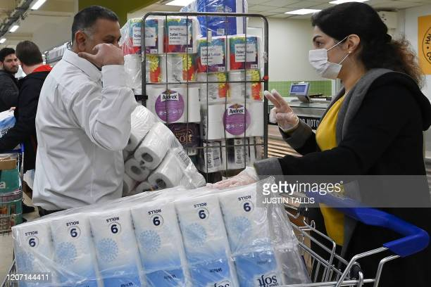 """Woman wearing a mask gesture """"two"""" to confirm the limit set by this supermarket in London for toilet paper packs on March 14 as consumers worry about..."""