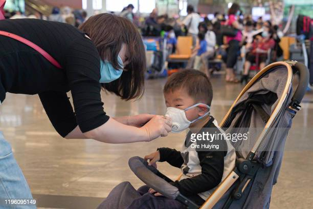 Woman wearing a mask helps her son put on his mask at Changi Airport on January 25, 2020 in Singapore. Yesterday Singapore confirmed its third case...