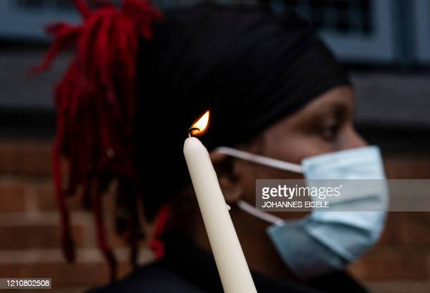A woman wearing a mask holds a candle while taking part in a vigil outside Queensboro Correctional Facility on April 23 2020 in New York City The...
