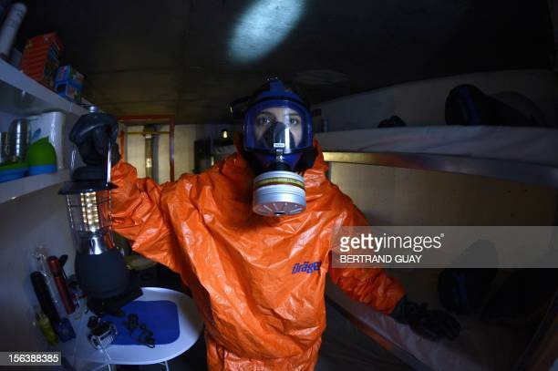 A woman wearing a mask holds a lamp in a nuclear shelter displayed in Paris on November 14 as part of a television show entitled 'Familles...