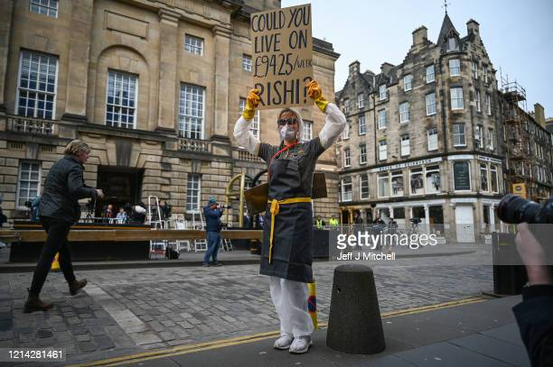 A woman wearing a mask holds a sign which asks Chancellor Rishi Sunak if he could live on the statutory sick pay rate for employees £9425 per week on...