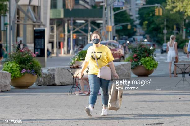 A woman wearing a mask is seen walking near Lincoln Center as the city continues Phase 4 of reopening following restrictions imposed to slow the...