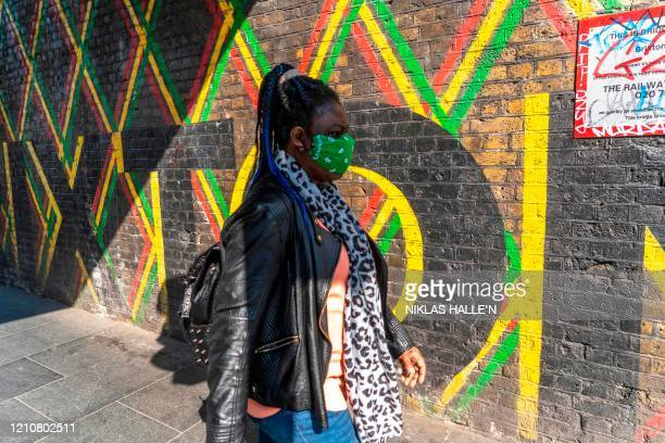 A woman wearing a mask is seen walking past a mural in Brixton south London on April 23 2020 as life in Britain continues under a lockdown designed...