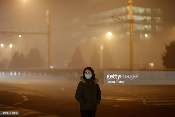 A woman wearing a mask on a polluted evening on November 30 2015 in Beijing China The representatives of the governments of more than 190 countries...