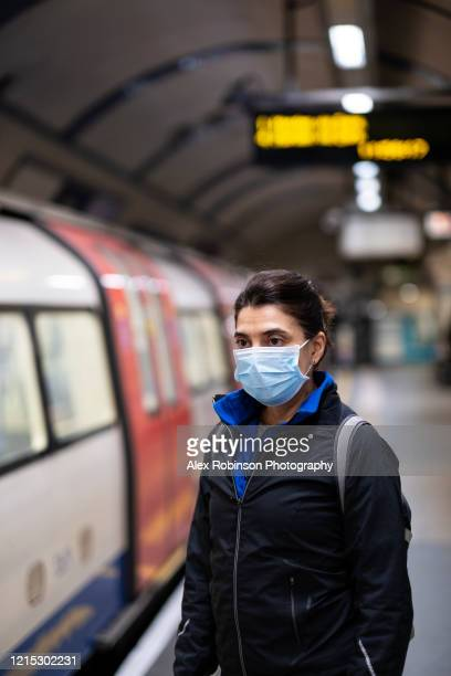 woman wearing a mask on the london subway or tube - tube stock pictures, royalty-free photos & images