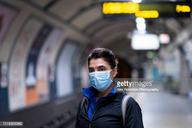 woman wearing a mask on the london subway or tube - ロックダウン ストックフォトと画像