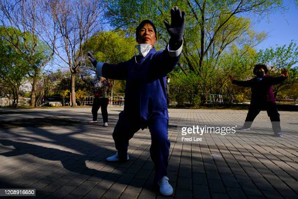 A woman wearing a mask performs Tai Chi wearing a mask as part of precautionary measures against the spread of the COVID19 on April 02 2020 in...