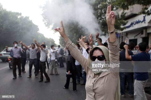 A woman wearing a mask raises her arms in protest as demonstrators gather in the streets on July 9 2009 in Tehran Iran Following recent unrest in the...