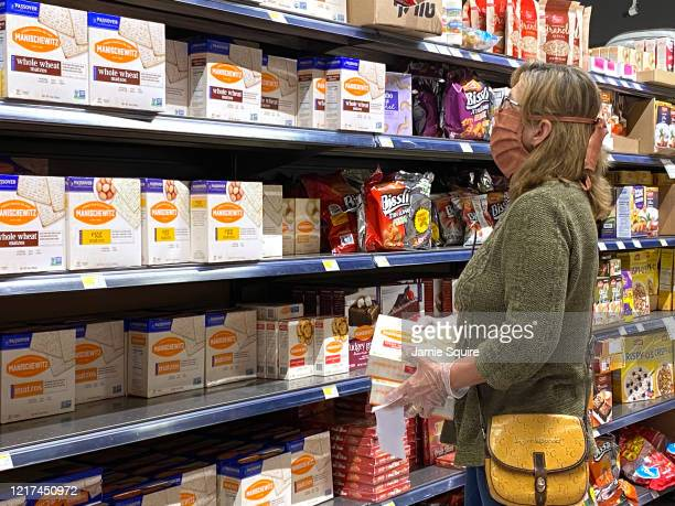 A woman wearing a mask shops for Passover items at a grocery store during the coronavirus pandemic on April 07 2020 in Overland Park Kansas The...
