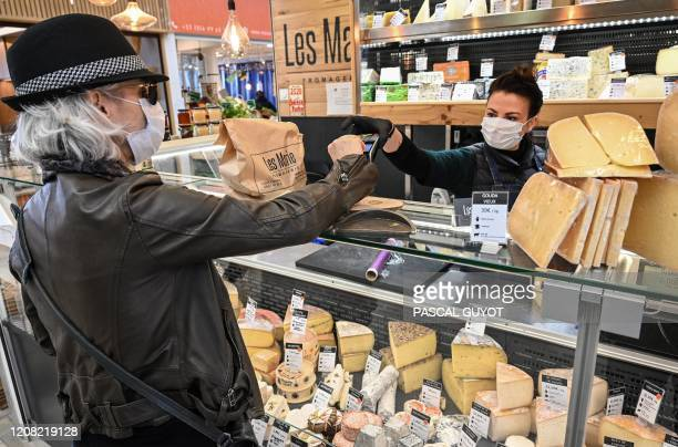 Woman wearing a mask shops in a cheese store in the center of Montpellier, on March 25 as the country is under lockdown to stop the spread of...