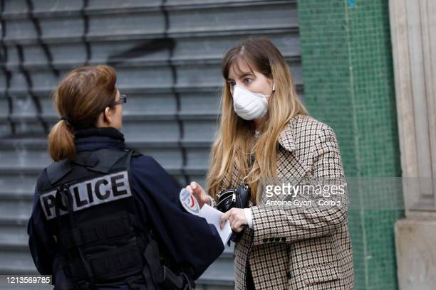 A woman wearing a mask speaks to a police officer on March 19 2020 in Paris France As of today995 people have tested positive for COVID19 including...