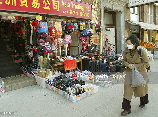 Woman, wearing a mask to protect against SARS, shops in Toronto's China Town April 25, 2003 in Toronto. The probable cases of SARS in Toronto...