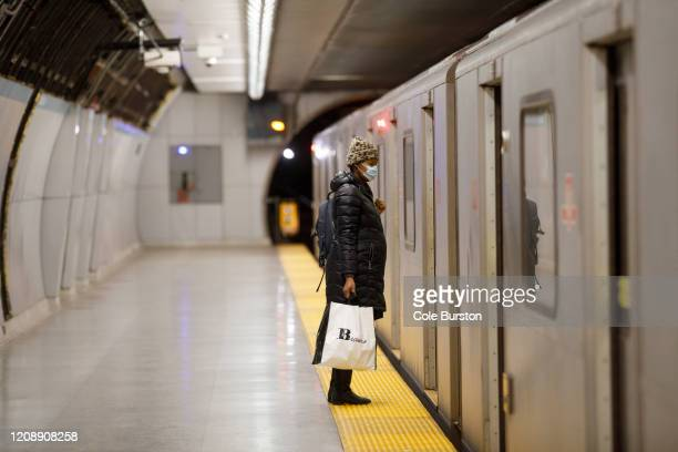 Woman wearing a mask waits to board a subway car during morning commuting hours as Toronto copes with a shutdown due to the Coronavirus, on April 1,...