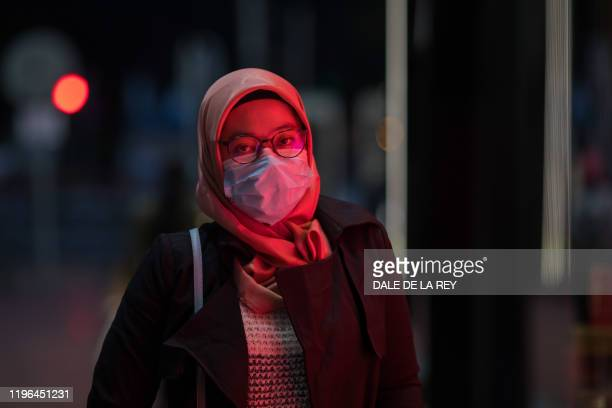 A woman wearing a mask walks along a street in a shopping district in Hong Kong on January 26 as a preventative measure following a coronavirus...