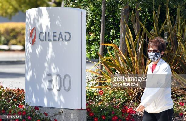 Woman wearing a mask walks by Gilead Sciences headquarters sign in Foster City, California on April 30, 2020. - Gilead Science's remdesivir, one of...