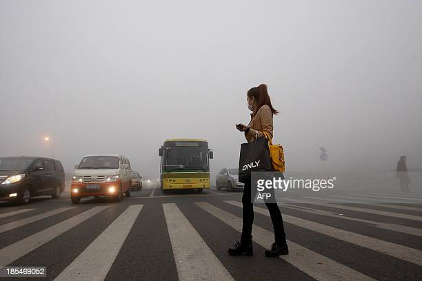 A woman wearing a mask walks in the smog in Harbin northeast China's Heilongjiang province on October 21 2013 Choking clouds of pollution blanketed...
