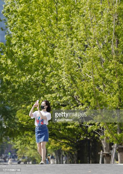 Woman wearing a mask walks in Yokohama on a hot day on May 2 during the Golden Week holidays under a state of emergency declared over the coronavirus...