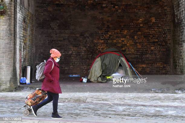Woman wearing a mask walks past a homeless tent in Bradford City Center on February 12, 2021 in Bradford, England.