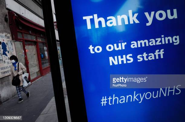 Woman wearing a mask walks past a message of thanks to the staff of the National Health Service , displayed on the digital advertising screen of a...