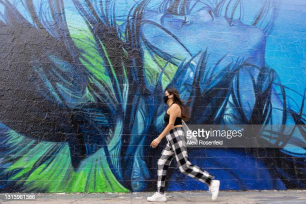 Woman wearing a mask walks past a mural advertising Billie Eilish's 'The Worlds A Little Blurry' on Apple TV on Melrose Avenue amid the coronavirus...