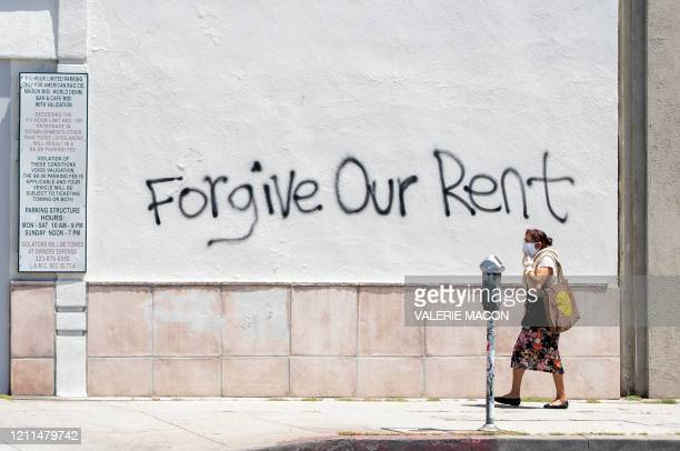 Woman wearing a mask walks past a wall bearing a graffiti asking for rent forgiveness on La Brea Ave on National May Day amid the Covid-19 pandemic,...
