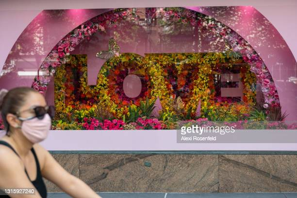 """Woman wearing a mask walks past the """"love"""" window at the Macy's Flower Show at Macy's Herald Square amid the coronavirus pandemic on May 02, 2021 in..."""