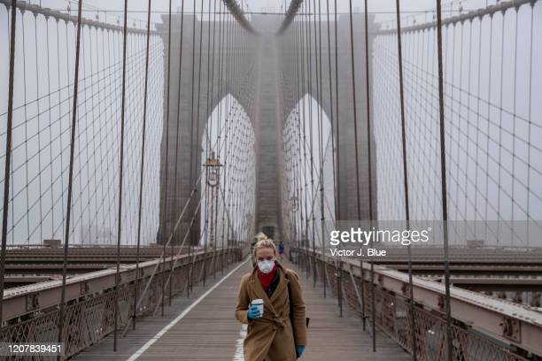 A woman wearing a mask walks the Brooklyn Bridge in the midst of the coronavirus outbreak on March 20 2020 in New York City The economic situation in...