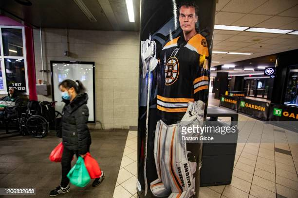 Woman wearing a mask walks through North Station near a poster of Bruins goalie Tuukka Rask and the TD Garden in Boston on March 12, 2020. The NHL...