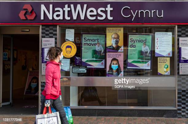 Woman wearing a mask while carrying shopping bags walks past a NatWest bank in Wales, UK. Eight more people have died with coronavirus in Wales and...