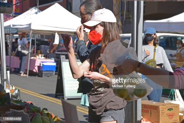 Woman wearing a mask while shopping at the Hollywood Farmers Market on November 15, 2020 in Los Angeles, California. Cities across the United States...