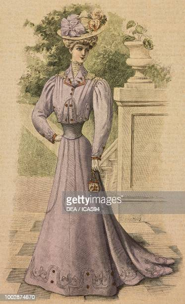 Woman wearing a mauve Drap walking dress halftrain skirt bolero with lace inserts and a hat with flowers creation by Martial and Armand colored...