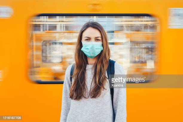 woman wearing a medical mask in a subway - protective face mask stock pictures, royalty-free photos & images