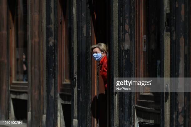 Woman wearing a medical mask looks out from a shop doorway, in Krakow's center. On Sunday, April 19 in Krakow, Poland.
