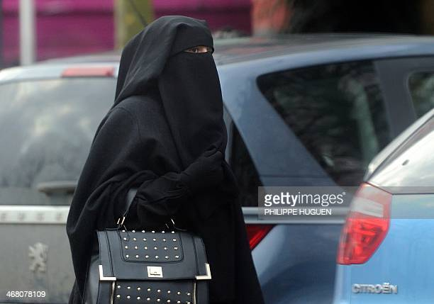 A woman wearing a niqab a type of full veil as she walks in a street in the center of Roubaix on January 9 2014 AFP PHOTO / PHILIPPE HUGUEN