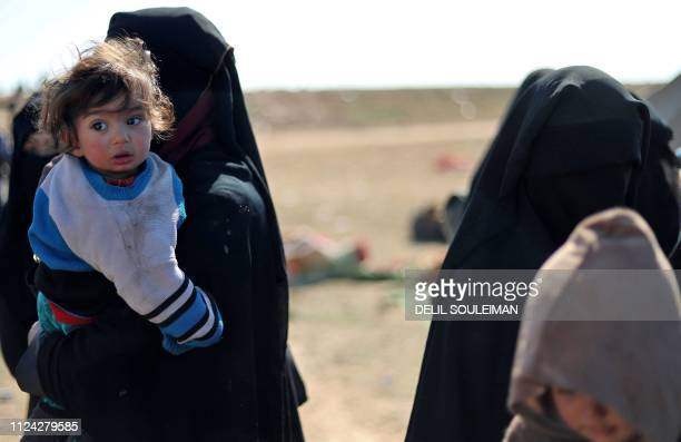 A woman wearing a niqab carries a child as civilians who are fleeing from the battered Islamic Stateheld holdout of Baghouz in the eastern Syrian...