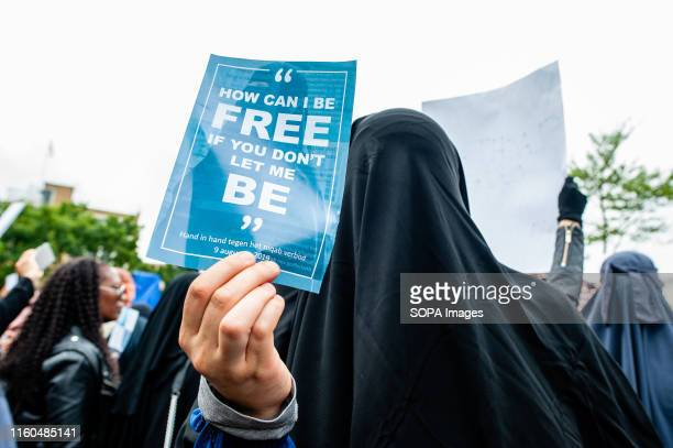 A woman wearing a niqab holds a placard that says How can I be free if you don't let me be during the protest Hundreds of people gathered in The...