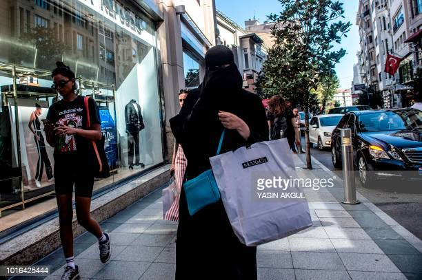 Woman wearing a niqab, holds shopping bags as she walks in the streets of Istanbul on August 13, 2018. - The collapse of the Turkish lira has caused...