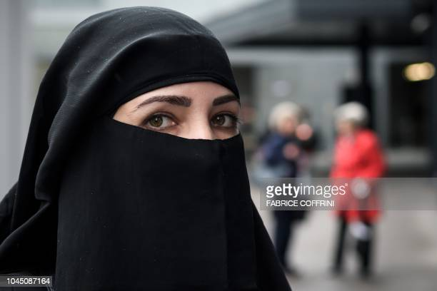 A woman wearing a niqab looks on during a protest by a FrenchAlgerian businessman and political activist on October 3 2018 in St Gallen by following...