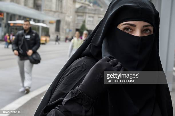 A woman wearing a niqab poses during a protest in St Gallen on October 3 2018 by French Algerian businessman and political activist Rachid Nekkaz...