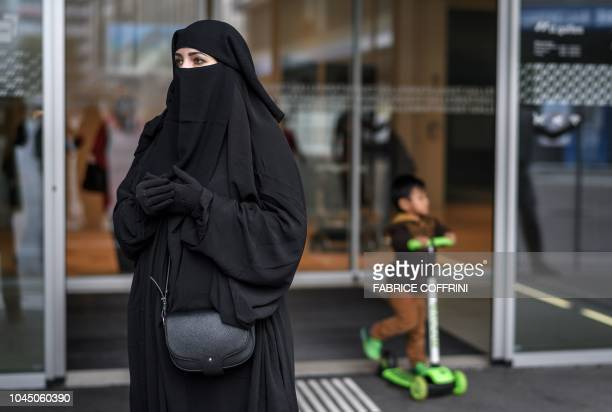 Woman wearing a niqab poses in front of the town hall of St. Gallen during a protest on October 3, 2018 by French Algerian businessman and political...
