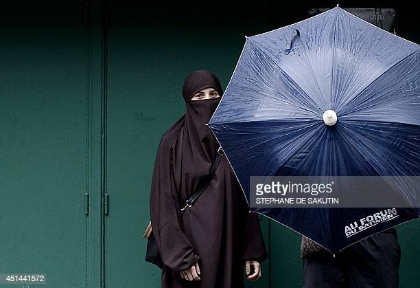 A woman wearing a niqab poses next to her husband in Paris on June 29 2014 The high section of the European Court of Human Rights located in the...