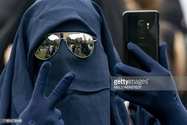 Woman wearing a niqab takes a selfie while flashing the victory sign as she takes part in a demonstration against the ban of a face-covering veil, in...