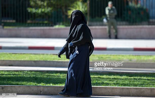 Woman wearing a niqab walks along a street in Rabat on January 15, 2017. Morocco's ban on the sale and production of burqa full-face Muslim veils...