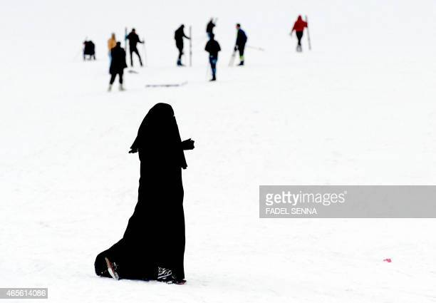 A woman wearing a niqab walks in the snow at the Oukaimeden ski resort in the Atlas Mountains 30 kilometres from the popular tourist resort of...