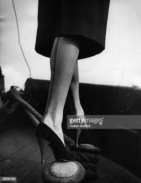 A woman wearing a pair of seamed stockings balancing on a post on a boat